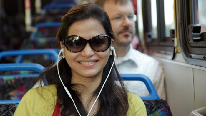 smiling woman listening to music on the bus, man behind her looking out the window